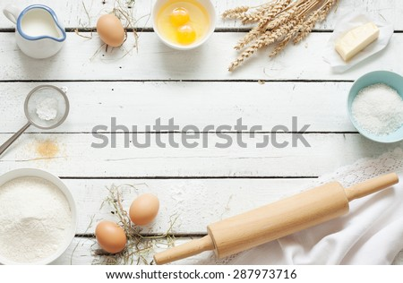 Baking cake in rustic kitchen - dough recipe ingredients (eggs, flour, milk, butter, sugar) on white planked wooden table from above. Background layout with free text space.