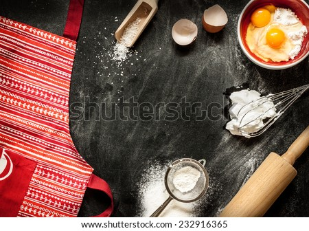 Baking cake ingredients. Apron, bowl, flour, eggs, egg whites foam, eggbeater, rolling pin and eggshells on black chalkboard from above. Cooking course poster background - layout with free text space.