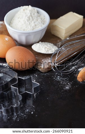 Baking cake ingredients with raw eggs, rolling pin, flour and cookie cutters on black background