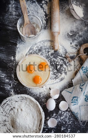 Baking cake or cupcakes ingredients - bowl, flour, eggs, egg whites foam and eggshells on black chalkboard from above. Cooking course or kitchen mess poster concept.