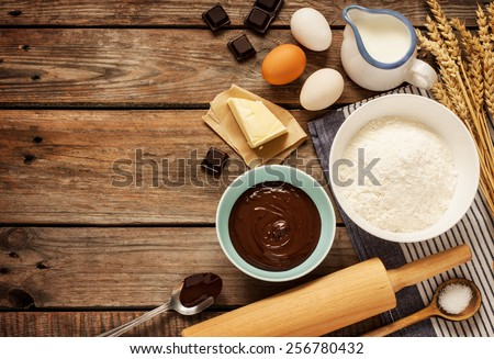 Baking chocolate cake in rural or rustic kitchen. Dough recipe ingredients (eggs, flour, milk, butter, sugar) on vintage wood table from above. Background layout with free text space.