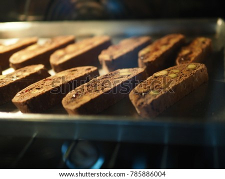 Baking chocolate pistachio biscotti for holiday desserts idea and great for dipping in coffee! (close up, selective focus, blurred space for text) #785886004