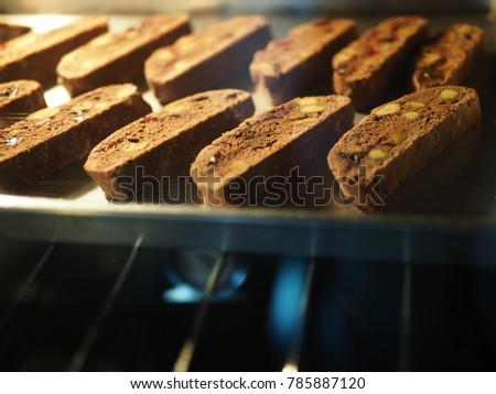 Baking chocolate pistachio biscotti for holiday desserts idea and great for dipping in coffee! (close up, selective focus, blurred space for text) #785887120