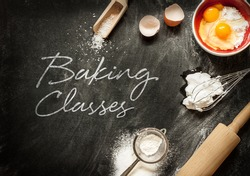 Baking classes poster design with cake ingredients on black chalkboard from above. Bowl, flour, eggs, egg whites foam, eggbeater, rolling pin and eggshells.