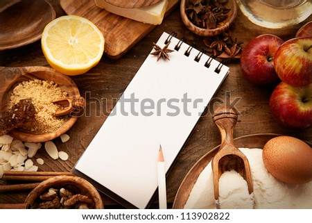 Baking concept background with paper for notes. Christmas and winter cookies ingredients.Baking pastry and cookies: apples, spices, sugar, eggs on wood