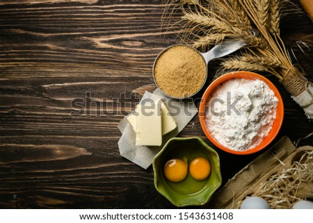 Baking concept - baking ingredients butter, flour, sugar, eggs on rustic wood background, top view #1543631408