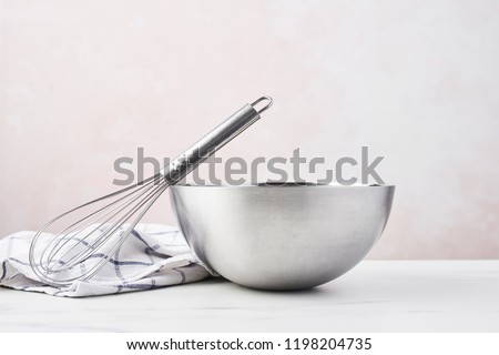 Baking concept. Bowl with a whisk and dishcloth on white marble table over pink background with copy space. #1198204735