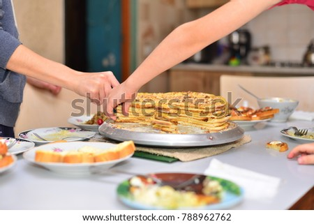 Baking concept. Female hands cutting butter with knife on the table