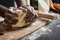 Baking concept. Hard working unrecognizable black male prepares pastry by himself, kneads dough on wooden counter with flour and rolling pin. Male African American cook bakes bread or delicious bun