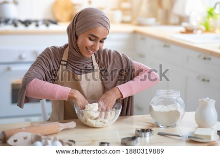 Baking Concept. Smiling Muslim Woman In Hijab Kneading Dough For Pie In Kitchen, Preparing Homemade Pastry, Happy Islamic Lady In Headscarf And Apron Enjoying Cooking Homemade Food, Copy Space