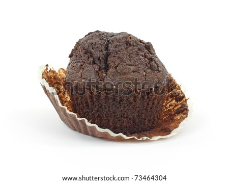 Baking cup being removed from double fudge chocolate muffin. - stock photo