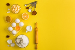 Baking flat lay background with white eggs, eggshells, yolk, a cup of 