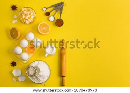 Baking flat lay background with white eggs, eggshells, yolk, a cup of floor, a cup of butter, milk, lemon and kitchen tool sieve, rolling pin and measuring spoons with spices on yellow.