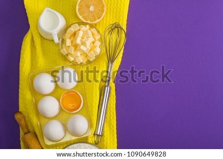 Baking flat lay composition with white eggs, yolk, a cup of butter,   milk, lemon and kitchen tool sieve, rolling pin and whisk on yellow   and violet background. Place for copy space.