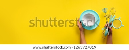 Baking flat lay. Female hands holding plate, bowl, kitchen tools, sieve, rolling pin, spatula and bruch on yellow background. Banner with copy space.