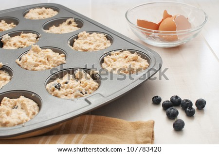 Baking form with dough, blueberries, cracked eggs