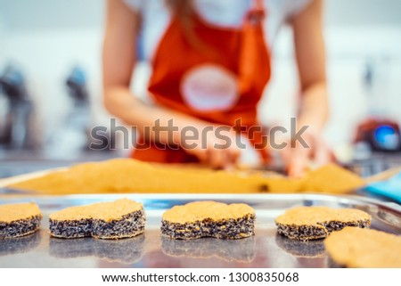 Baking heart shaped cookies or cakes. Woman in background blurred. Bakery concept for valentine. #1300835068