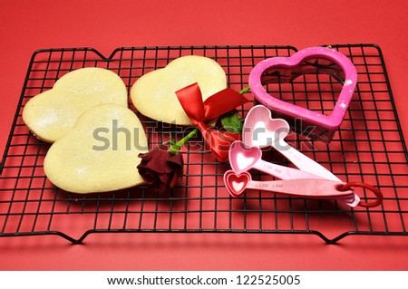 Baking home-made heart shape shortbread cookies, with cookie cutter and baking accessories for that special someone on Valentine's Day set against a red background.