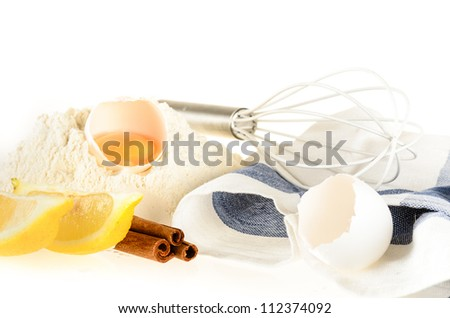 Baking ingredients and tools: eggs, flour, lemon wages, cinnamon sticks, whisk and kitchen towel