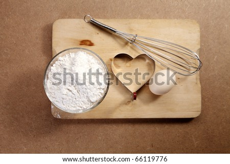 Baking ingredients and utensils isolated on chopping board.
