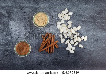 Baking ingredients. Cinnamon, nutmeg, ginger, pumpkin seeds, top view on a gray background.