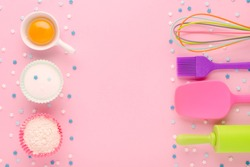 baking ingredients, egg, flour, sugar, sweet decoration and kitchen tools on pink background with copy space