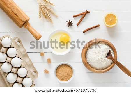 Baking ingredients: flour, eggs, brown sugar, spices, lemon, rolling pin and golden wheat ears on white wooden table. Top view