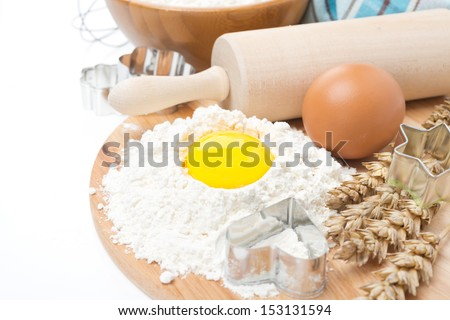 baking ingredients - flour, eggs, rolling pin and baking forms, isolated