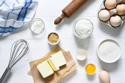 Baking ingredients: flour, eggs, sugar with a rolling pin on a light white wood background.