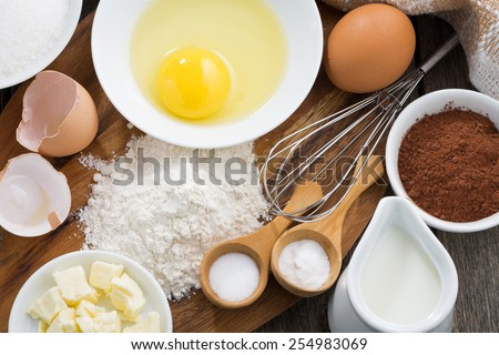 Baking ingredients on a wooden board, top view, close-up