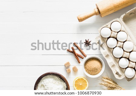 Baking ingredients on white table. White eggs, rolling pin, flour, sugar and spices. Home baking concept, baking cake or cookies ingredients