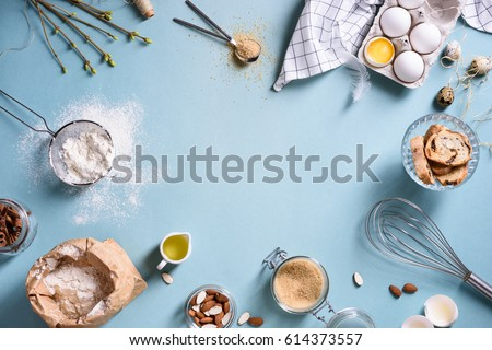 Baking or cooking background frame. Ingredients, kitchen items for baking cakes. Kitchen utensils, flour, eggs, almond, cinnamon, oil. Text space, top view.