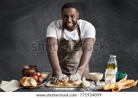 Baking process. Cheerful dark skinned African American male wears apron, kneads dough with great enthusiasm, being content to recieve praise from chef for endeavour and hard work in restaurant #771934099