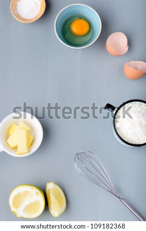 Baking raw ingredients flour, eggs, sugar shot from overhead on a grey background