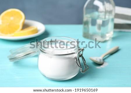 Baking soda in glass jar on light blue wooden table Photo stock ©