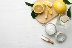 Baking soda, vinegar and cut lemons on white wooden table, flat lay. Space for text