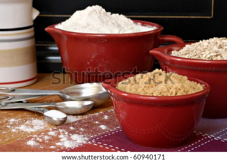 Baking still life of ceramic measuring cups and stainless steel spoons filled with ingredients.  Flour dusted in foreground.  Macro with shallow dof.