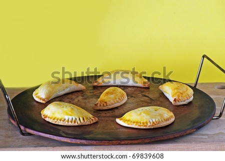 Baking stone with meat-filled Panama style empanadas against yellow background.
