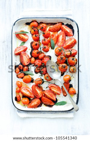 Baking tray filled with delicious juicy oven roasted organic tomatoes with fresh sage leaf herb and olive oil