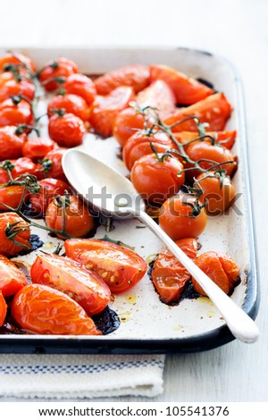 Baking tray filled with delicious juicy oven roasted tomatoes with large serving spoon, focus on front wedges of tomato