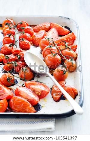 Baking tray filled with delicious juicy oven roasted tomatoes with large serving spoon, focus on spoon