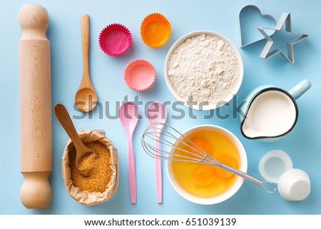 Baking utensils and ingredients. Egg yolk, brown sugar, milk, flour, whisker, spoons, cinnamon, bowl, rolling pin, cupcake paper cup, molds, sweet decoration elements. Top view. Flat lay - Shutterstock ID 651039139
