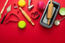Baking utensils, rolling pin, cupcake molds, cookies cutters over red background. Abstract baking concept