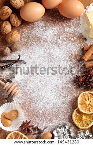 Baking utensils, spices and food ingredients on wooden background with copy space.