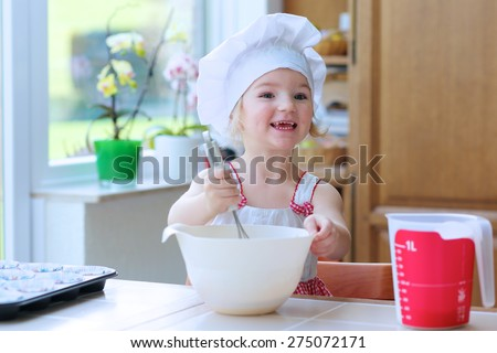 Baking with children: little happy kid, adorable toddler girl in white chef hat mixing dough ingredients in bowl helping mother to prepare delicious pastry in the kitchen