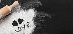 Baking with love. Black background with flour, rolling pin, text love, and heart shape on dark kitchen board top view for Valentine's day cooking. Flat lay style with space for text. banner