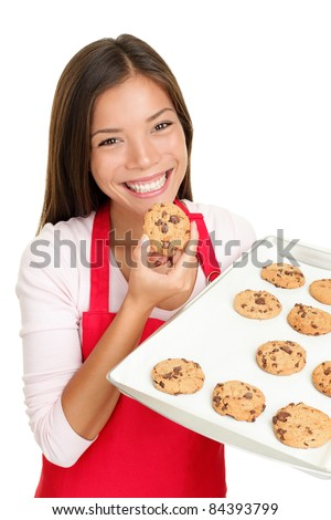 baking woman eating cookies fresh from the oven. Happy smiling mixed race Chinese Asian / white Caucasian cooking at home. Isolated on white background.
