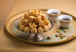 Baklava and arabic black coffee presented in a golden tray with few pistachio nuts. Beautiful photo of Turkish or Mediterranean sweet served with coffee.