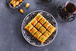Baklava. Ramadan Dessert. Traditional Arabic dessert with nuts and honey, cup of tea on a concrete table. Top view