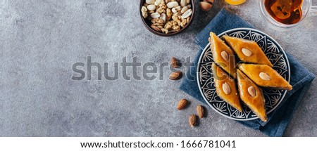 Baklava. Ramadan Dessert. Traditional Arabic dessert with nuts and honey, cup of tea on a wooden concrete table. Top view, copy space